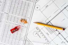 Architekturzeichnungen, ein Dreieck und ein Bleistiftspitzer mit einem Bleistift Lizenzfreie Stockbilder