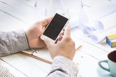 Architetti disponibili di Smartphone con l'attrezzatura del fondo per lavoro Fine in su fotografia stock libera da diritti