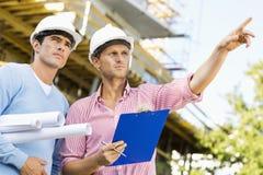 Architetti maschii con il modello e la lavagna per appunti che funzionano al sito fotografie stock libere da diritti