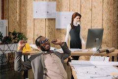 architetto afroamericano del handscome che allunga nella sedia mentre il suo funzionamento del collega Immagini Stock