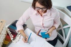 Architetto arredatore della donna, impianti con i campioni dei tessuti per le tende e ciechi fotografia stock libera da diritti