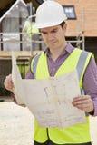 Architetto On Building Site che esamina i piani per la Camera Immagine Stock