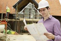 Architetto On Building Site che esamina le piante della casa Fotografia Stock