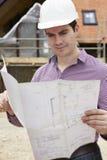 Architetto On Building Site che esamina le piante della casa immagine stock