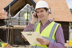 Architetto On Building Site che per mezzo del telefono cellulare Fotografia Stock