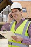 Architetto On Building Site che per mezzo del telefono cellulare Fotografie Stock