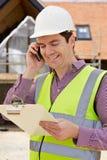 Architetto On Building Site che per mezzo del telefono cellulare fotografie stock libere da diritti