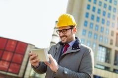 Architetto in casco protettivo facendo uso della compressa digitale immagini stock libere da diritti