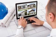 Architetto che esamina le progettazioni della casa sul computer portatile Fotografia Stock