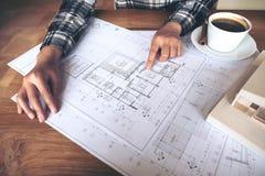 Architetto che lavora ad un modello di architettura con la carta da disegno del negozio e la tazza di caffè sulla tavola immagine stock libera da diritti
