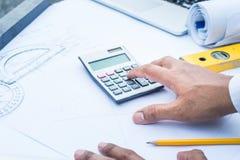 Architetto che lavora con il calcolatore sulla carta di progettazione di piano Fotografia Stock