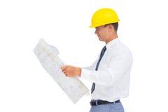 Architetto che legge un piano con il casco giallo fotografie stock libere da diritti