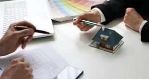 Architetto che mostra il nuovo modello della casa della famiglia al cliente archivi video