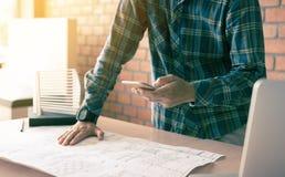 Architetto che sta scrivente sullo smartphone e lavorante in moderno di Immagine Stock