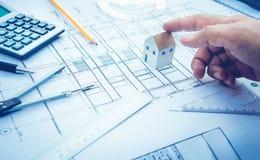 Architetto con il modello della casetta a disposizione e la progettazione di piano Concetto fotografie stock libere da diritti