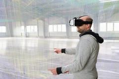 Architetto con la visiera di VR che esplora l'ambiente del fabbricato industriale Immagini Stock Libere da Diritti