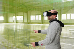 Architetto con la visiera di VR che esplora l'ambiente del fabbricato industriale Fotografia Stock