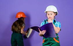Architetto dell'ingegnere del costruttore Lavoratore del bambino in casco Sviluppo di puericultura piccole ragazze che riparano i immagini stock