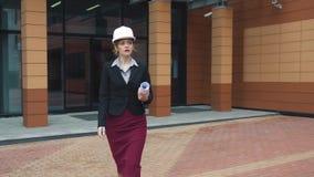 Architetto della giovane donna in un casco della costruzione con i modelli in mani Costruttore in casco Donna di affari sul lavor archivi video
