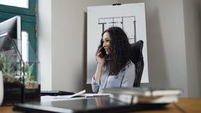 Architetto femminile caucasico che parla sullo Smart Phone durante il giorno del lavoro nell'ufficio archivi video
