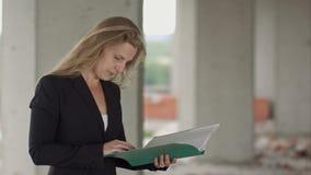 Architetto femminile che studia i progetti mentre visitando il grande cantiere stock footage