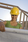 Architetto femminile Reviewing Blueprint Immagini Stock