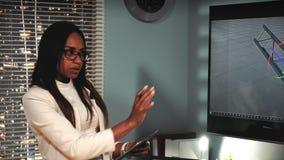 Architetto nero femminile che discute con il modello del collega 3D della componente del ponte sul grande schermo video d archivio