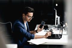 Architetto professionista vestito in un vestito che parla tramite il telefono e gli impianti sul computer portatile nell'ufficio immagini stock libere da diritti