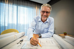 Architetto Working On Blueprint allo scrittorio Immagine Stock