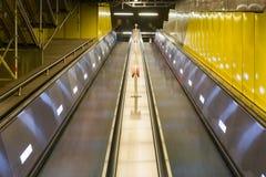 Architettura alta lunga Inte del sottopassaggio della scala mobile gialla luminosa del metallo Fotografie Stock Libere da Diritti