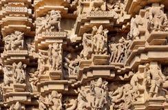 Architettura indiana con le figure della gente di dancing, dei, animali Sollievi del tempio storico in Khajuraho fotografie stock libere da diritti