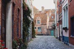 Architettura medievale tradizionale, via pavimentata stretta con le case con mattoni a vista con i tetti piastrellati rossi fotografia stock libera da diritti
