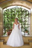 Architict dress. A bride standing under a arch in her dress Royalty Free Stock Image