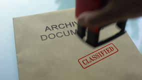 Archival documents classified, hand stamping seal on folder with documents. Stock footage stock video