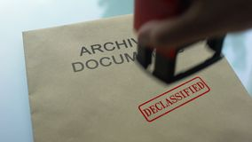 Archival documents declassified, hand stamping seal on folder with documents. Stock footage stock video