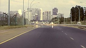 Archival Durban highway driving. Durban, South Africa - Circa 1981: street view with vintage cars on the Durban highway in city traffic. Historical archival stock video