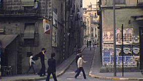 Archival Tarragona streets. Tarragona, Spain - Circa 1970: old streets of Tarragona city. People in vintage dress and vintage cars on the road. Archival of stock video footage