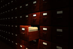 Archive Room. Open file drawer in a dark room filled with file cabinets Stock Photo