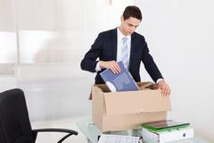Archivi dell'imballaggio dell'uomo d'affari in scatola di cartone in ufficio immagine stock libera da diritti
