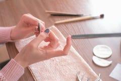 Archivio di chiodo dei chiodi delle limature della donna Mani del primo piano Strumenti sulla tavola Immagine Stock Libera da Diritti