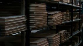 Archivistische ruimte of boekopslagruimte in de kelderverdieping Een vrouw in een blauwe T-shirt komt omhoog en doet de lichten u stock video