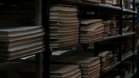 Archiwalny pokoju lub książki depository w piwnicie Kobieta w błękitnej koszulce wchodzić na górę daleko światła i obraca Półki n zbiory wideo