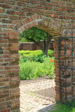 Archway in brick wall. Beautiful arched doorway in old brick wall, with black wrought iron gate leading into the lush garden beyond Stock Photos