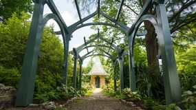 Arched path to gazebo. An archway covered path leading to a green roofed gazebo Royalty Free Stock Image