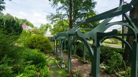 Arched path to gazebo. An archway covered path leading to a green roofed gazebo Stock Image
