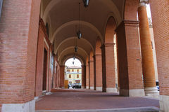 Archway with hanging lanterns of ancient building on Cavour squa Stock Images