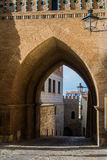 An archway of a mudejar style tower, old buildings and a lantern at the wall at medieval town Teruel. At Aragon province, Spain Stock Photos
