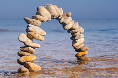 Archway of pebbles. On the sea surface Royalty Free Stock Photography