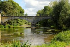 Archway road bridge. Slow flowing river with age old archway road bridge Royalty Free Stock Photos