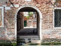 Archway through to a street. Entrance to a street off of a small canal in Venice Italy Stock Image